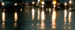 Wet streets at night reflecting automobile lights