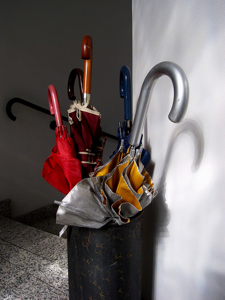 An umbrella stand with many umbrellas