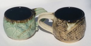 Two ceramic cups, one with a fairy, one with a winged cat.