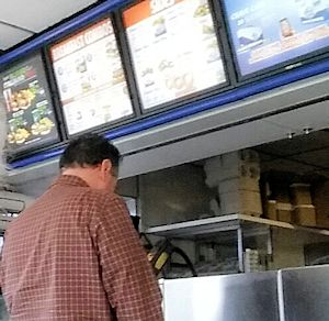 A man from behind, standing at a fast food counter.