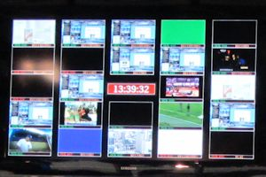 A TV control room big screen showing mutiple feeds at once.